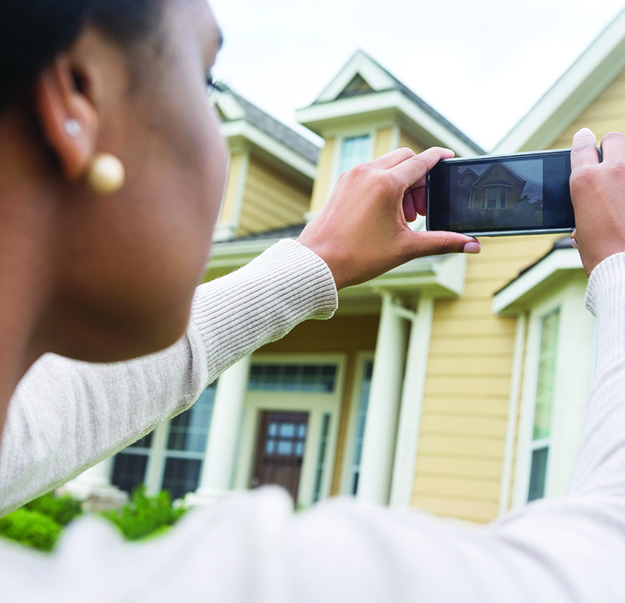 Woman taking a photo of house