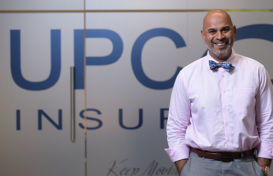 Employee in front of UPC wall